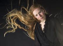 Femme avec le vent soufflant par de longs cheveux blonds Images stock