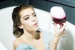 Femme avec le verre dans le bain Image libre de droits