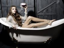 Femme avec le verre dans le bain Photographie stock