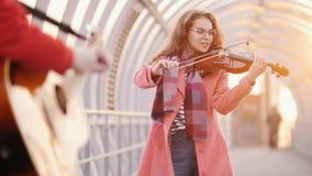 Femme avec le violon et l'homme blured avec la guitare jouant la musique classique sur le passage banque de vidéos