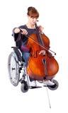 Femme avec le violoncelle sur le fauteuil roulant image libre de droits
