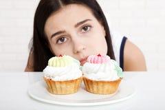 Femme avec le visage de plan rapproché de gâteau Les belles femmes regarde tristement le gâteau Femme asiatique Foyer sélectif images stock