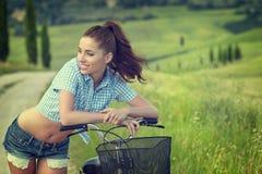 Femme avec le vélo dans une route de campagne Photos stock