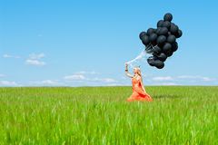 Femme avec les ballons noirs marchant sur l'herbe verte images stock
