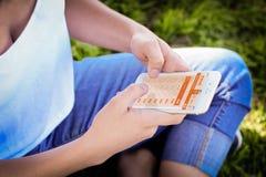 Femme avec les billets d'avion de achat de smartphone sur l'appli mobile photos stock