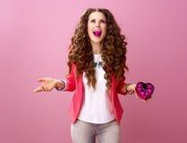 Femme avec les bonbons au chocolat en forme de coeur dans la bouche Image stock