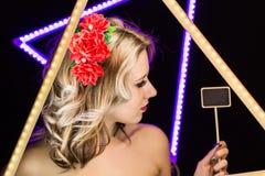 Femme avec les boucles blondes et jante d'empilement sur un fond foncé tenant un signe Images stock