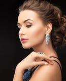 Femme avec les boucles d'oreille et l'anneau Photo stock