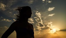 Femme avec les bras ouverts se tenant à la plage de bord de la mer de coucher du soleil Image stock