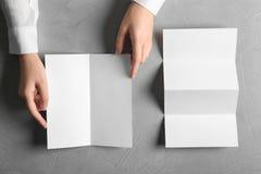 Femme avec les brochures vides sur le fond gris images stock