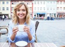Femme avec les cheveux blonds appréciant un café chaud Photos libres de droits