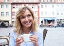 Femme avec les cheveux blonds buvant d'un café et regardant autour Photo libre de droits