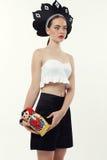 Femme avec les cheveux blonds dans le chapeau national russe tenant la poupée de matrioshka Images stock