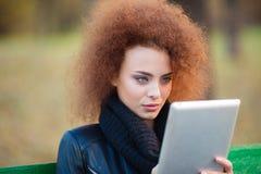 Femme avec les cheveux bouclés utilisant la tablette dehors Photographie stock libre de droits