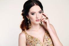 Femme avec les cheveux foncés portant la robe et le bijou luxueux de paillette Photographie stock