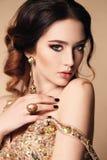 Femme avec les cheveux foncés portant la robe et le bijou luxueux de paillette Photo libre de droits