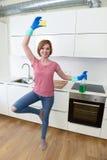Femme avec les cheveux rouges dans les gants de lavage en caoutchouc tenant la bouteille et le récureur de jet de nettoyage photos stock