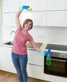 Femme avec les cheveux rouges dans les gants de lavage en caoutchouc tenant la bouteille et le récureur de jet de nettoyage images libres de droits