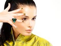 Femme avec les clous d'or et l'émeraude de pierre précieuse Photo libre de droits