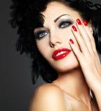 Femme avec les clous rouges et la coiffure créative Photographie stock libre de droits