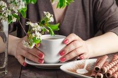 Femme avec les clous rouges reposant et tenant une tasse de café chaude Photos libres de droits