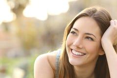 Femme avec les dents blanches pensant et regardant en longueur Photographie stock libre de droits