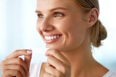 Femme avec les dents blanches saines utilisant des dents blanchissant la bande Images libres de droits