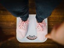 Femme avec les espadrilles roses sur l'échelle de poids de salle de bains Images stock