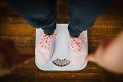 Femme avec les espadrilles roses sur l'échelle de poids de salle de bains Photographie stock