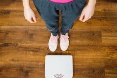 Femme avec les espadrilles roses sur l'échelle de poids de salle de bains Images libres de droits