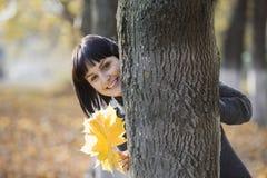 Femme avec les feuilles automnales derrière l'arbre Photographie stock libre de droits