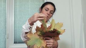 Femme avec les feuilles colorées d'arbre d'érable banque de vidéos