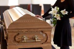 Femme avec les fleurs et le cercueil de lis à l'enterrement photographie stock libre de droits
