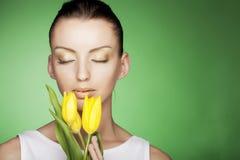 Femme avec les fleurs jaunes sur le fond vert Image stock