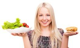 Femme avec les légumes et l'hamburger Photographie stock libre de droits
