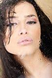 Femme avec les languettes sensuelles derrière la glace Image libre de droits