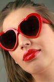 Femme avec les lunettes de soleil en forme de coeur Photo stock