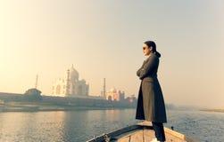 Femme avec les lunettes de soleil de port se tenant sur un bateau avec Taj Mahal à l'arrière-plan photo libre de droits
