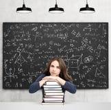 Femme avec les mains et la tête sur la pile de la pensée de livres Photo stock