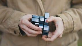 Femme avec les mains tendres dans le rétro manteau brun clair de vintage accomplissant la vue de face de recherche de cube-rubik  banque de vidéos