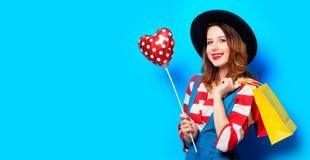 Femme avec les paniers et le jouet de forme de coeur Photo stock