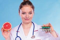 Femme avec les pilules et le pamplemousse de perte de poids de régime photographie stock libre de droits