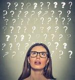 Femme avec les points d'interrogation perplexes d'expression de visage au-dessus de sa tête recherchant Photo libre de droits