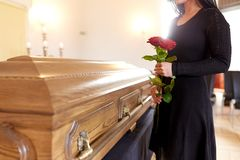 Femme avec les roses rouges et le cercueil à l'enterrement image stock