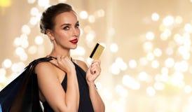 Femme avec les sacs à provisions par la carte de crédit et photographie stock