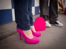 Femme avec les talons et l'homme roses dans les mandrins noirs Photographie stock libre de droits