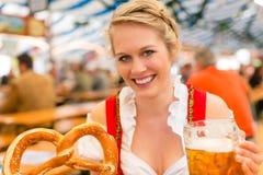 Femme avec les vêtements ou le dirndl bavarois dans la tente de bière image libre de droits