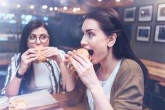Femme avec plaisir attirante mangeant un hamburger Image libre de droits