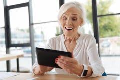 Femme avec plaisir gaie regardant l'écran de comprimé Photo libre de droits