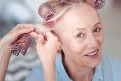 Femme avec plaisir heureuse à l'aide des rouleaux de cheveux Photos stock
